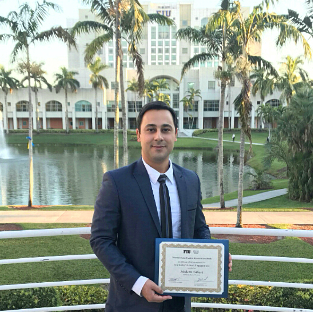Photo of Mohsen Taheri holding his awarded UGS Provost Award for Graduate Student Engagement